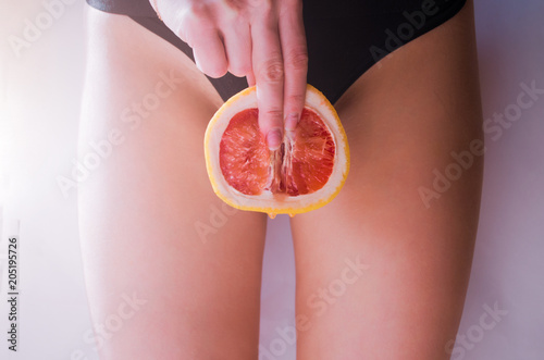 Fotografia A woman is holding a grapefruit by her panties