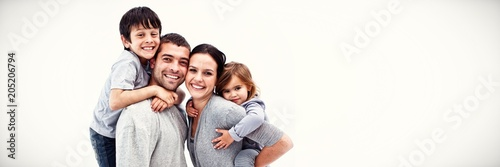 Obraz Happy parents giving children piggyback rides - fototapety do salonu