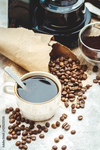 Variety things for prepare coffee. Roasted beans, ground coffee, scoop, electric coffee machine and assortment of sweets and spices to eat with on light background.