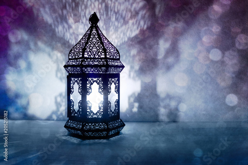 Ornamental Arabic lantern with burning candle glowing at night and glittering blue bokeh lights. Festive greeting card, invitation for Muslim holy month Ramadan Kareem. Blurred party background
