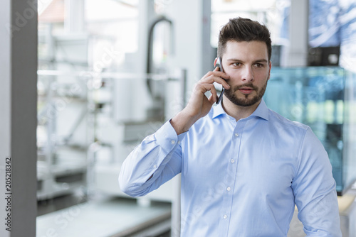 Portrait of man on cell phone in factory