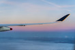 Wing of a plane above the clouds with mountains in background