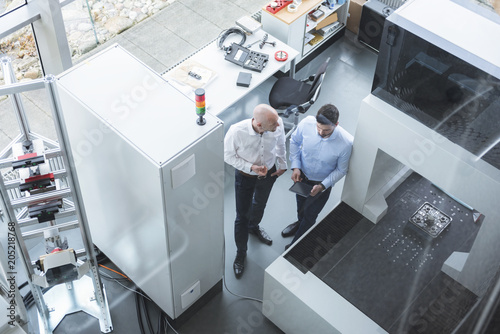 Two businessmen with tablet talking in industrial office