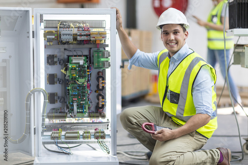 Portrait of smiling technician working on a box with circuit boards