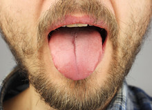 Man With A Beard Opened His Mouth And Stuck Out His Tongue