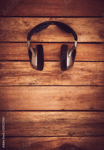Papiers peints A top view of a set of wireless headphones lying on a rustic wood table, desk. Styling and grain effect added to image.