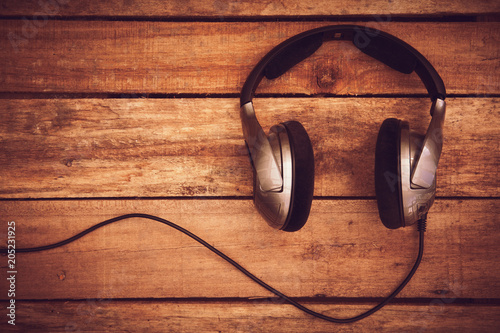 Papiers peints A top view of a set of wired headphones lying on a rustic wood table, desk. Styling and grain effect added to image.