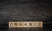 The Word Organic, Consisting Of Light Wooden Square Panels On A Dark Wooden Background