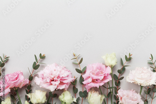 Poster Fleur Beautiful floral border of pastel flowers and green eucalyptus leaves on gray table top view. Flat lay style.