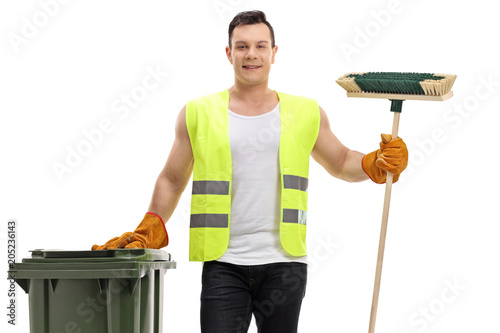 Waste collector holding a garbage bin and a broom