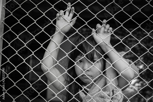 Fotografie, Obraz  The sad Asian girl child, while sitting alone in cage was imprisoned make no fre