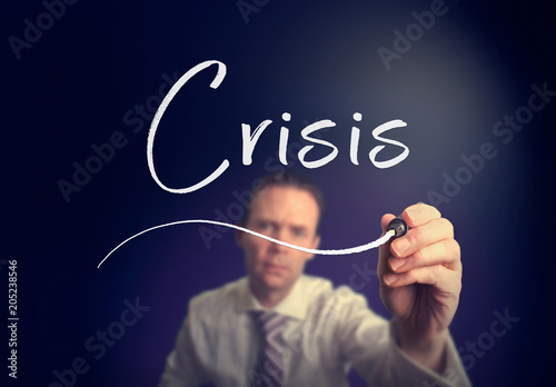 Photo A businessman writing a Crisis concept with a white pen on a clear screen