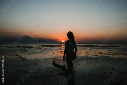 Foto op Aluminium Grijze traf. .Young woman on vacation in the Gili Islands enjoying a colorful sunset in Indonesia. Photograph and vacation.