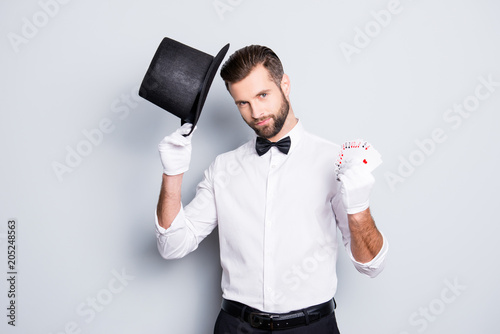 Portrait of virile harsh illusionist with stubble and modern hairstyle, holding tophat and set of cards in hands, looking at camera, isolated in grey background