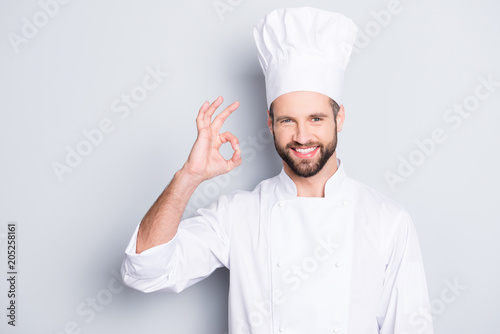 Portrait of cheerful joyful chef cook in beret and white outfit with stubble looking at camera showing ok sign, approve, advice menu isolated on grey background