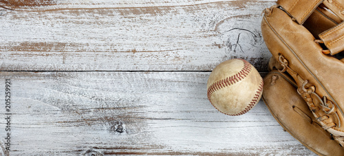 Flat lay view of old baseball and mitt on white rustic wooden boards