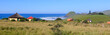 canvas print picture - Panoramic view of a rondawel, traditional thatched roofed hut near Coffee Bay on the Wild Coast in Eastern Cape, South Africa, with a view over the Indian Ocean