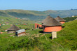canvas print picture - Rondawels, traditional thatched-roofed huts scattered through the grassy hills in a village near Coffee Bay on the Wild Coast in Eastern Cape, South Africa