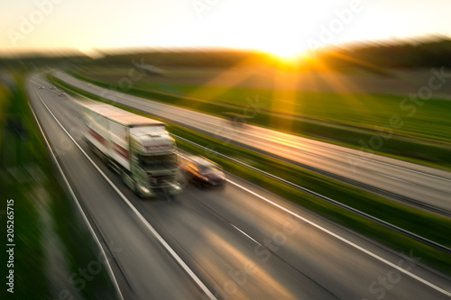 Obraz Truck and cars in motion blur on the freeway towards the setting sun. Rush hour on the motorway in Finland - fototapety do salonu