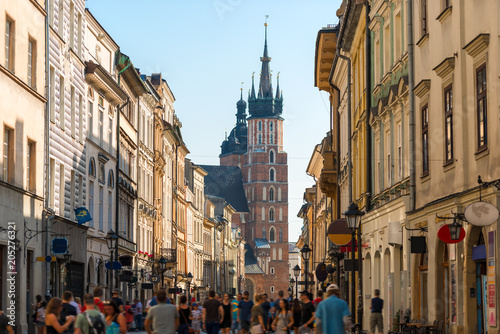 Fototapeta a crowd of tourists on Florian street, view of the Mariinsky church in the center of Krakow, Poland obraz