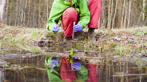 Valokuva  Scientist ecologist in the forest taking sample of water for chemical analysis