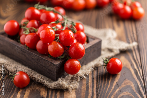 Fototapeta Small red cherry tomatoes on rustic background. Cherry tomatoes on the vine obraz