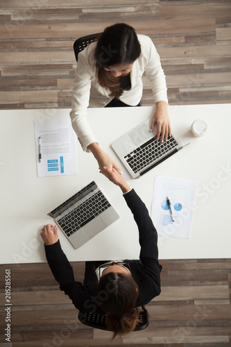 Fotografía  Top view of two female associates or CEOs handshaking greeting each other or making agreement and starting successful cooperation together