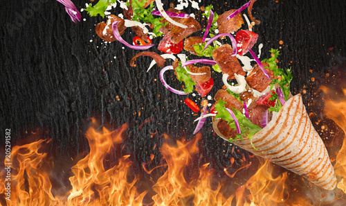 Turkish Kebab yufka with flying ingredients and flames.