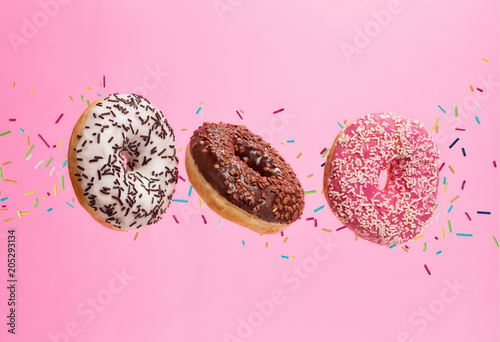 Fotografía  Flying sweet donuts isolated on pink background.