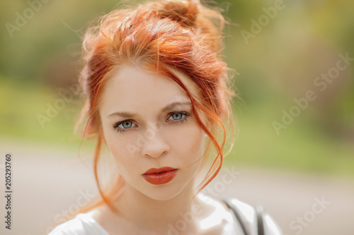 beautiful young woman with red hair, outside in a park in the sunlight, looking Wallpaper Mural