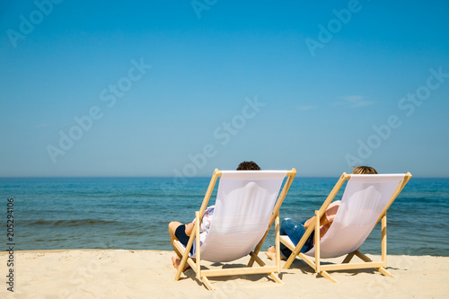 Tablou Canvas Woman and man relaxing on beach