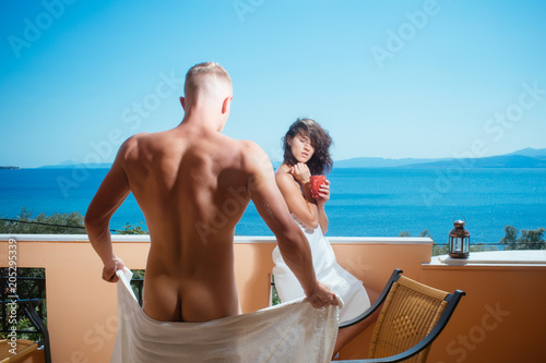 Foto op Plexiglas Akt Couple in love drinking coffee on balcony, nature and sea on background. Man and lady in bathrobe hold cup and drink. Vacation and relax concept. Couple enjoy view on sea and skyline on sunny day
