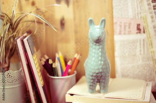 Poster Lama Figure of llama on a work table with books and pencils, back to school concept