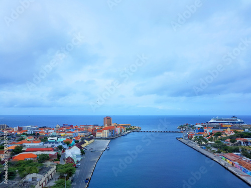 aerial view of the coastline city of Willemstad, capital of Curazao, with colorful buildings and blue sea and sky Wallpaper Mural