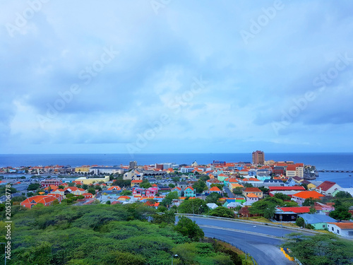 Photo aerial view of the coastline city of Willemstad, capital of Curazao, with colorful buildings and blue sea and sky