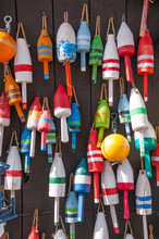 Colorful Fishing Buoys Hanging On Outdoor Wall