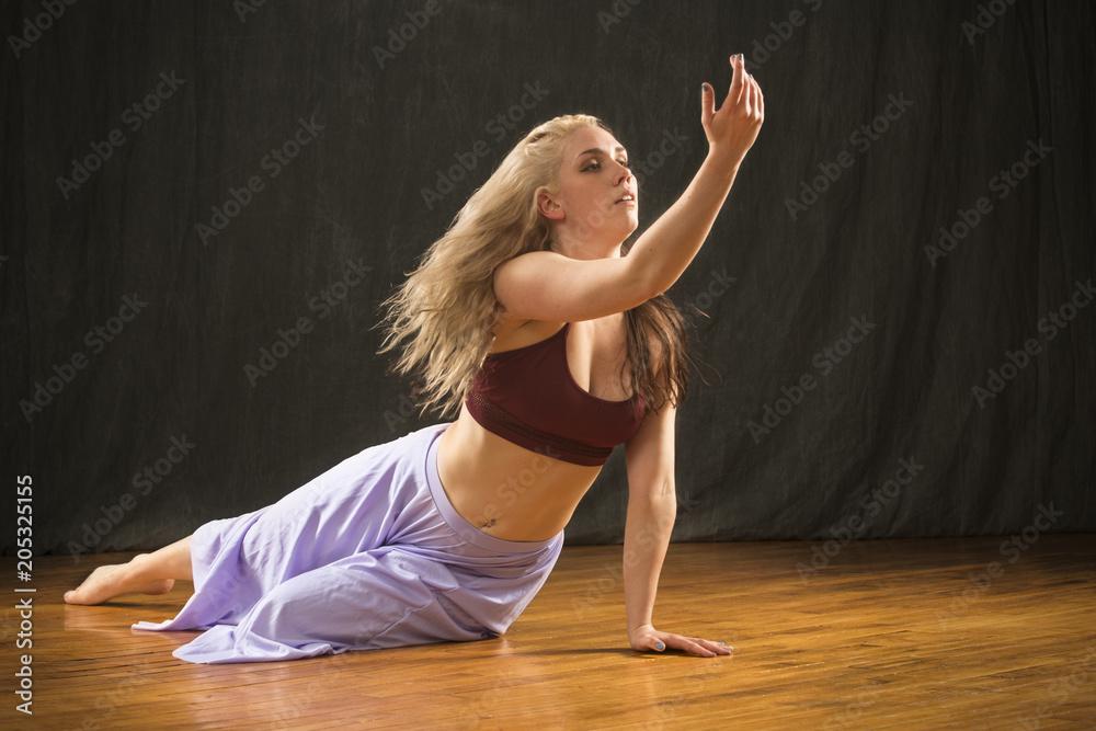 Fototapeta Young woman dancer performing dramatic floor work.