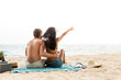 Young couple sitting at the beach relaxing and having a good time together on summer vacations