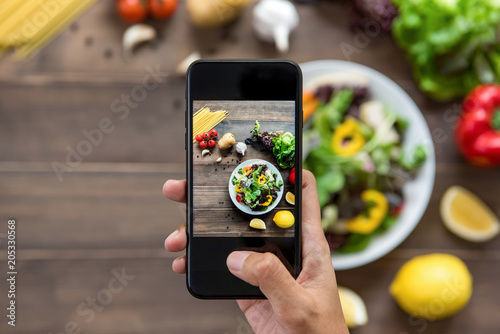 Food blogger using smartphone taking photo of beautiful salad