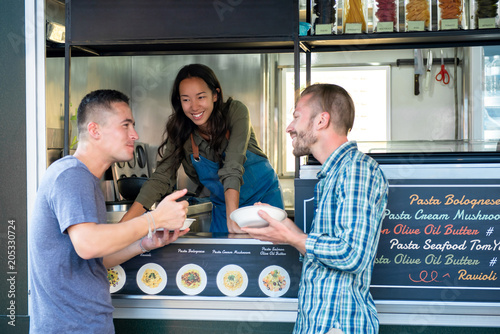 Two friends enjoy eating pasta from food truck
