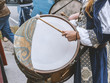 Side view of man in medieval costume plays drum in the street.