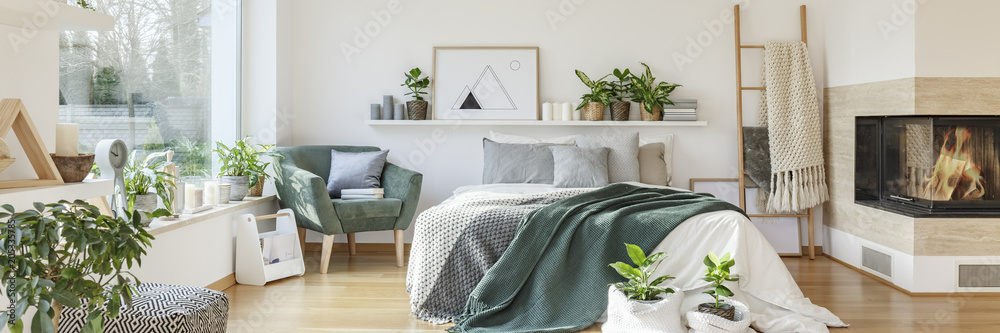Fototapety, obrazy: Natural bedroom interior with a cozy, white bed with decorative cushions standing between a fireplace and a green armchair. Real photo