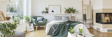 Natural Bedroom Interior With A Cozy, White Bed With Decorative Cushions Standing Between A Fireplace And A Green Armchair. Real Photo