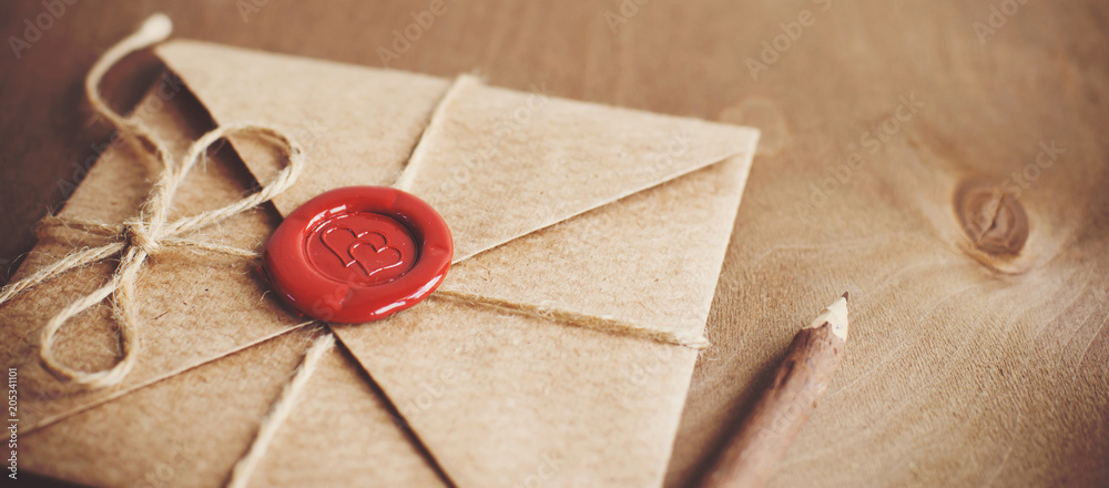 Fototapeta love letter in a craft envelope with a sealing wax seal in the form of a heart on a wooden background. Free space