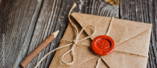 Fototapeta love letter in a craft envelope with a sealing wax seal in the form of a heart on a wooden background