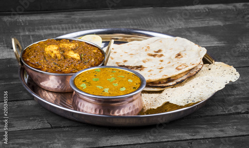 Fotografie, Obraz  Indian Traditional Thali Food Dal Makhani Served with Chapati, Papad, Kadai Paneer or Lemon Also Know as Dal Makhni or Daal Makhani is a Popular Dish From Punjab