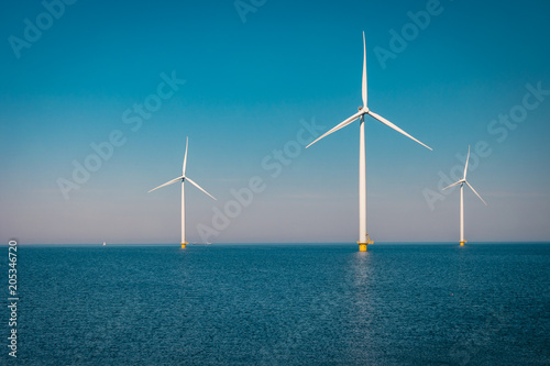 Fotografia  Offshore and Onshore Windmill farm in the ocean ,windmills isolated at sea on a