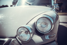 Close Up Front View Of Old Classic Car Headlight Is Outdoor With Bokeh Background