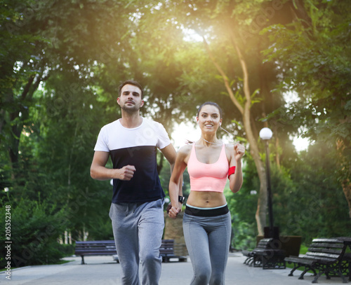Couple jogging outdoors working out in the park