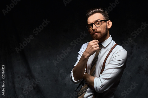 Fototapeta Young stylish hipster with cool hairstyle and beard dressed in white shirt and suspenders is thinking of a new creative idea looking at viewer obraz